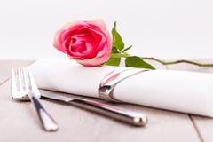 Gedeck mit einer einzelnen Rosarose Stockbilder