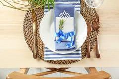 Gedeck mit lila Farbserviette, Karte und Blumendekor Stockbild
