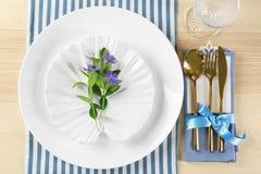 Gedeck mit lila Farbserviette und Blumendekor Lizenzfreie Stockbilder