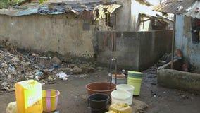 Gedeeld waterpunt, vuile krottenwijkwoning, Conakry stock video