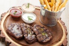 Gedeelte van BBQ rundvleesfilethaakwerk mignon met sausen en gebraden aardappels Royalty-vrije Stock Foto's
