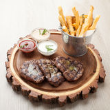 Gedeelte van BBQ rundvleesfilethaakwerk mignon met sausen en gebraden aardappels Stock Afbeeldingen