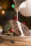 Gedeelte van de Pudding van Kerstmis met het Gieten van Room Stock Afbeeldingen