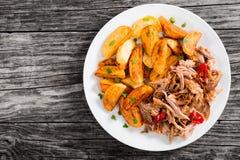 Gedeelte van getrokken langzaam-gekookt vlees met gebraden aardappelwiggen royalty-vrije stock foto's