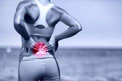 Gedeeltelijk desaturated beeld van gespannen mannelijke rug Atletische lopende vrouw met rugletsel Stock Afbeelding