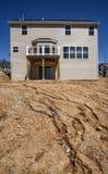 Gedeeltelijk gebeëindigd nieuw twee-verhaal huis in aanbouw in woononderverdeling met modderige heuvel, het vinyl opruimen en ven stock afbeelding