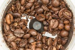 Gedeeltelijk gemalen gebraden donkere koffiebonen in een automatische koffiemolen, voedselachtergrond Stock Afbeelding