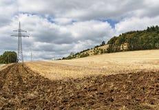 Gedeeltelijk geploegd gebied na de oogst met transmissietoren en beboste heuvel op de achtergrond Stock Foto