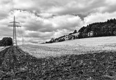Gedeeltelijk geploegd gebied na de oogst met transmissietoren en beboste heuvel op de achtergrond Royalty-vrije Stock Foto's