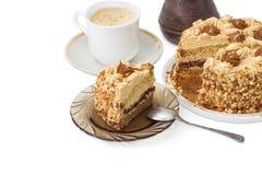 Gedeeltelijk gesneden gelaagd biscuitgebak op achtergrond van koffie royalty-vrije stock afbeelding