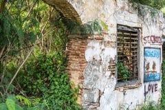 Gedeeltelijke bakstenen muur op verlaten plaats met graffiti Stock Afbeeldingen