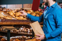 gedeeltelijke mening die van klant brood van brood nemen stock afbeeldingen