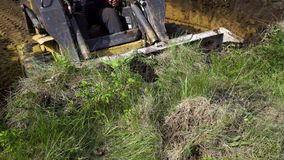 Gedeeltelijke mening van bulldozer die laag van grasrijke grond verwijderen tijdens de aardewerken stock video