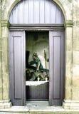 Gedeeltelijke mening van een zeer oud godsdienstig beeld van Christus binnen een portaal met gedeeltelijk gesloten houten deuren Royalty-vrije Stock Afbeelding