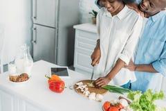 gedeeltelijke mening van samen het glimlachen van Afrikaans Amerikaans kokend ontbijt in keuken royalty-vrije stock afbeelding