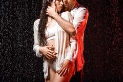 gedeeltelijke mening van sexy paar in witte overhemden die zich onder regen bevinden stock afbeelding