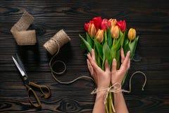 Gedeeltelijke mening van vrouwelijk handen, kabel, schaar en boeket van bloemen royalty-vrije stock foto's