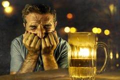 Gedeprimeerd alcoholisch mens het drinken verspild en het gedronken bier ontbrekende verzetten zich tegen in barbar bij nacht te  stock afbeelding