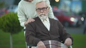 Gedeprimeerd gehandicapt bejaard mannetje die in rolstoel jonge vrouwelijke hand, familie strijken stock videobeelden