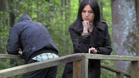 Gedeprimeerd paar in het park op de brug stock videobeelden