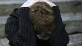 Gedeprimeerd schooljongen verbergend gezicht onder hoodie, slachtoffer van het bulling, dakloosheid stock videobeelden