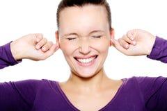 Gedeprimeerd vrouwelijk gezicht wat oren omhoog tegenhouden Royalty-vrije Stock Foto