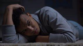 Gedeprimeerde Afrikaans-Amerikaanse tiener die aan eenzaamheid in donkere ruimte lijden, misbruik stock footage
