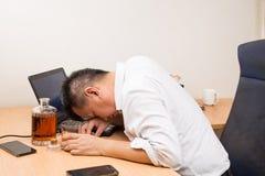 Gedeprimeerde Aziatische die bedrijfsleider op bureau wordt gedronken royalty-vrije stock afbeelding