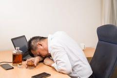 Gedeprimeerde Aziatische die bedrijfsleider op bureau wordt gedronken stock afbeelding