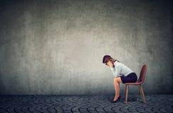 Gedeprimeerde bedrijfsvrouwenzitting op stoel en neer het kijken royalty-vrije stock foto