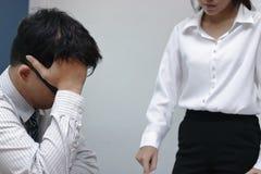 Gedeprimeerde beklemtoonde jonge Aziatische bedrijfsmens die gezicht behandelen die aan streng probleem lijden met collega in bur stock afbeeldingen