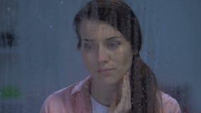 Gedeprimeerde dame die achter regenachtig venster schreeuwen die aan depressie na scheiding lijden stock footage