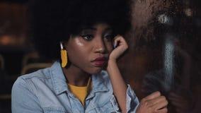 Gedeprimeerde, droevige younf Afrikaanse Amerikaanse vrouw die een openbaar vervoer berijden bij nacht Zij die uit het venster ki stock videobeelden