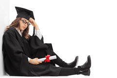 Gedeprimeerde gediplomeerde student met een diplomazitting op de vloer royalty-vrije stock foto's