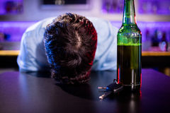 Gedeprimeerde gedronken mensenslaap met zijn hoofd op de lijst stock afbeeldingen