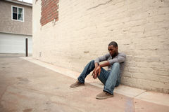 Gedeprimeerde Jonge Afrikaanse Amerikaanse Mens die opnieuw leunt Royalty-vrije Stock Foto