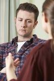 Gedeprimeerde Jonge Mens die aan Adviseur spreken stock foto