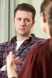 Gedeprimeerde Jonge Mens die aan Adviseur spreken stock afbeelding