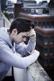 Gedeprimeerde Jonge Mens die Zelfmoord bovenop Lange Buildin overwegen royalty-vrije stock fotografie