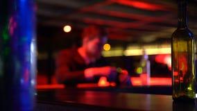 Gedeprimeerde jonge mens het drinken alcohol alleen in bar, mislukking, problemen in het leven stock footage