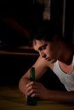 Gedeprimeerde jonge mens met bierfles stock afbeelding