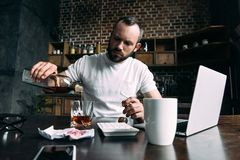 gedeprimeerde jonge mensen gietende whisky in glas na verbreken met meisje stock foto's