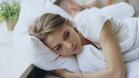 Gedeprimeerde jonge vrouw in bed liggen en feeeling die thuis verstoord na ruzie met haar boylfriend in bed stock videobeelden