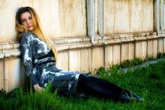 Gedeprimeerde jonge vrouw en grungy muur Stock Fotografie