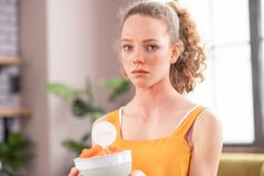 Gedeprimeerde jonge vrouw met paardestaart die ongelukkig met haar gezonde voeding zijn stock afbeelding
