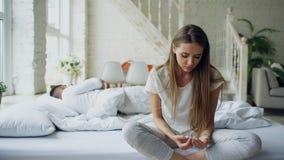 Gedeprimeerde jonge vrouwenzitting in bed en het schreeuwen terwijl haar boylfriend die in bed thuis liggen royalty-vrije stock fotografie