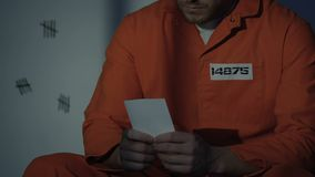 Gedeprimeerde Kaukasische gevangene in cel die foto, ontbrekende vrouw en kinderen bekijken stock videobeelden