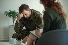 Gedeprimeerde militair met emotioneel probleem tijdens vergadering met psychotherapist royalty-vrije stock foto's