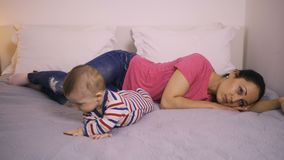 Gedeprimeerde moeder op bed met baby en weg het staren stock video