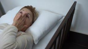 Gedeprimeerde oude geduldige afvegende scheuren die in ziekbed, vrijwilligers ondersteunende dame liggen stock videobeelden
